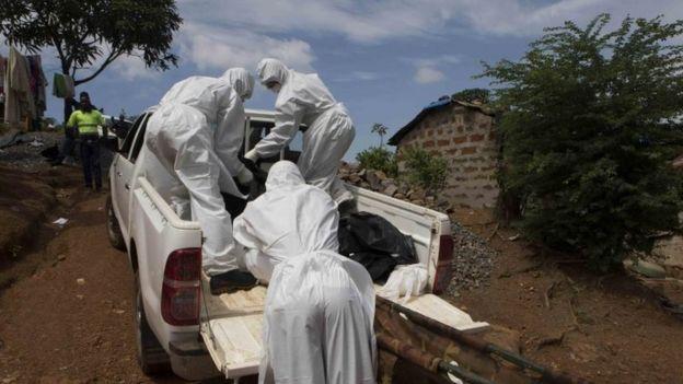 Koruyucu giysiler giyen bir mezar ekibi, Liberya'daki Freetown'da Ebola virüsünden öldüğünden şüphelenilen bir kişinin cesedini çıkarıyor (28 Eylül 2014)