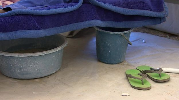 Two buckets next to a patient's bed