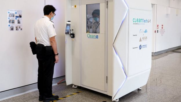 A member of staff goes through the CLeanTech full-body disinfection channel facility at Hong Kong International Airport, 24 April 2020