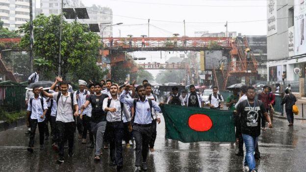 Grupo de estudiantes bajo la lluvia en una manifestación en la capital de Bangladesh, Daca.