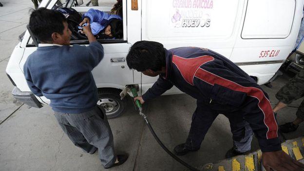 Un carro llenando el tanque de gasolina