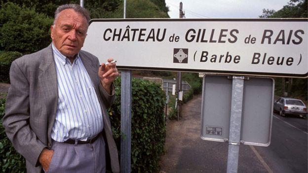 Gilbert Prouteau, autor de uma biografia de Gilles de Rais, em 1992, em frente a uma placa do Castelo do Barba Azul