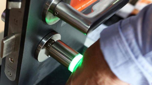 Una persona poniendo su brazo contra un lector de microchips