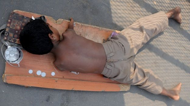 File photo: A handicapped child lies on a mat while begging for alms next to a few Indian rupee and paise coins given to him in Mumbai on December 7, 2011