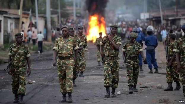 Burundian soldiers walk near a burning barricade erected by protesters as people demonstrate against the president's bid for a third term in power in Musaga, in the outskirts of Bujumbura, on April 27, 2015
