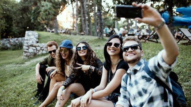 Grupo de millenials se toma una selfie.