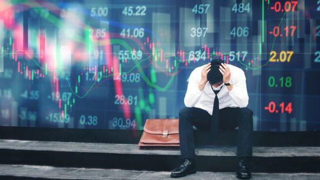 Homem com as mãos na cabeça, com números e gráficos econômicos de fundo