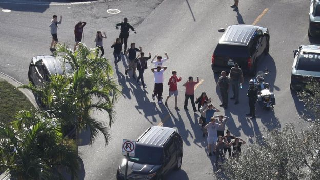 People are brought out of the Marjory Stoneman Douglas High School after a shooting at the school that reportedly killed and injured multiple people on February 14, 2018