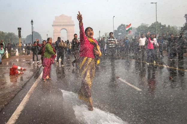 A protester chants slogans as she braces herself against the spray fired from police water canons during a protest against the Indian government's reaction to recent rape incidents in India, in front of India Gate on December 23, 2012 in New Delhi, India.