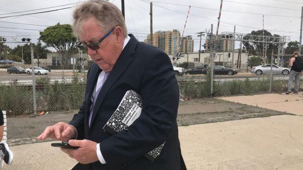 El padre de Edward Gallagher, mirando su teléfono.