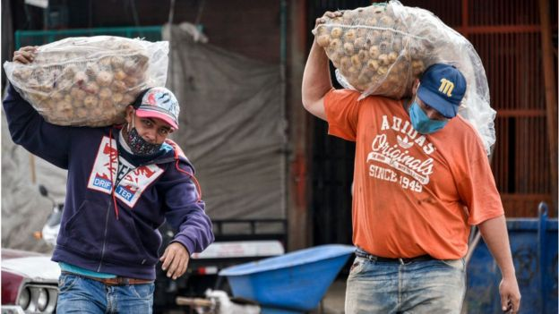 dois homens de máscaras carregando sacos de alimentos na rua