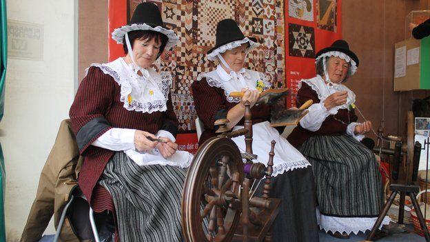 Maureen Preen (ar y dde), gydag Olwen Davies (canol) a Gwenno Jones, yn nyddu ar stondin Amgueddfa Cymru // Maureen Preen (right), with Olwen Davies (centre) and Gwenno Jones spinning a yarn on the National Museum of Wales stand