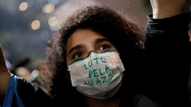 Manifestante em rua de São Paulo com máscara dizendo: 'Luto pela Amazônia'