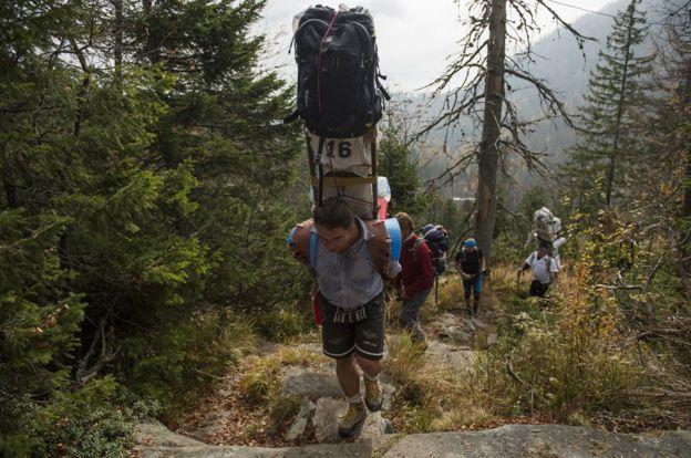 Sherpa subindo uma montanha carregando várias bolsas