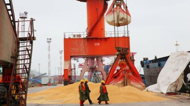 "Workers walk past imported soybeans at a port in Nantong in China""s eastern Jiangsu province on April 4, 2018"