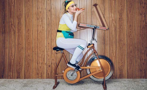 Mujer en bicicleta de ejercicio comiendo pizza