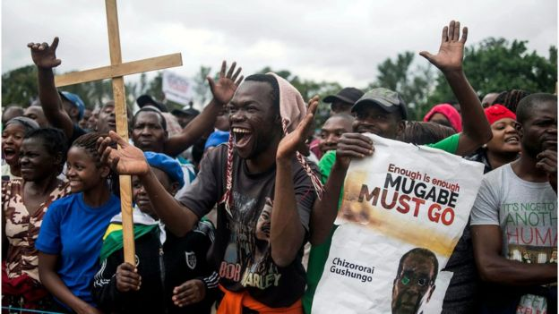 Protesters holding placards applaud and chant slogans at a rally in Harare to demand the resignation Robert Mugabe, 18 November.