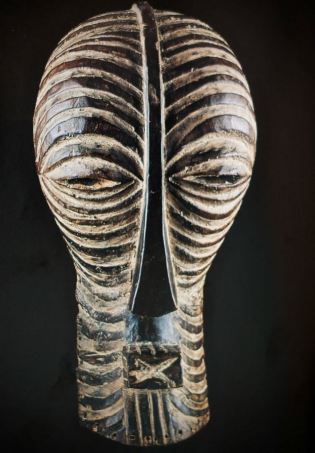 A carved wooded mask depicting an elongated face