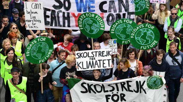 Greta Thunberg y otros adolescentes con pancartas en la huelga escolar de este viernes en Estocolmo