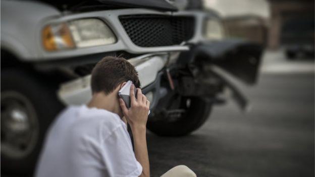 Joven llamando por teléfono después de un accidente.