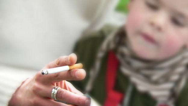 Niño junto a un adulto fumando