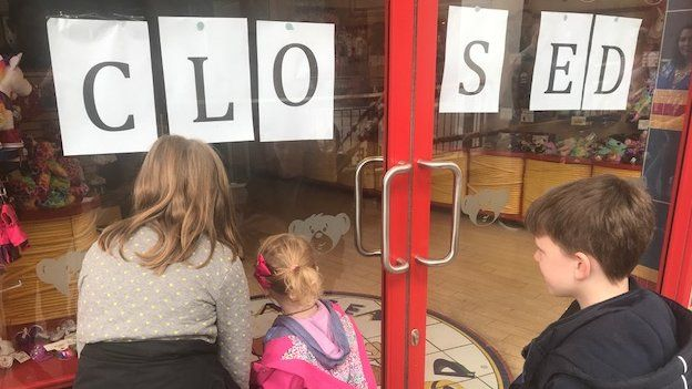 A mother and her children look through the window of the closed Build-a-Bear Workshop