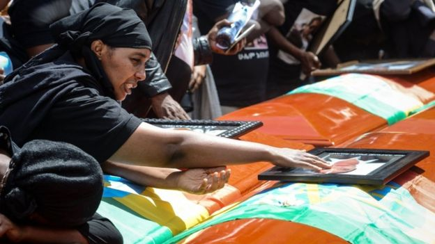 A mourner of victims of the Ethiopian Airlines crash touches a portrait on a coffin during the mass funeral at Holy Trinity Cathedral in Addis Ababa, on 17 March
