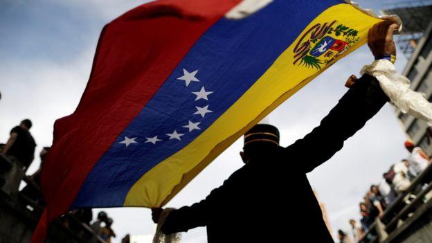 Hombre sostiene bandera venezolana durante una manifestación