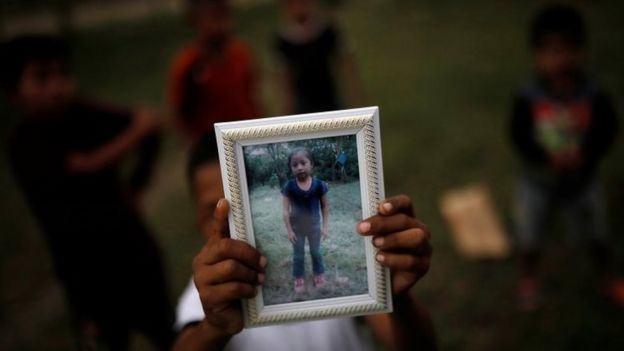Jakelin Caal's brother Abdel holds a picture of her sister outside their home in San Antonio Secortez. Photo: 22 December 2018