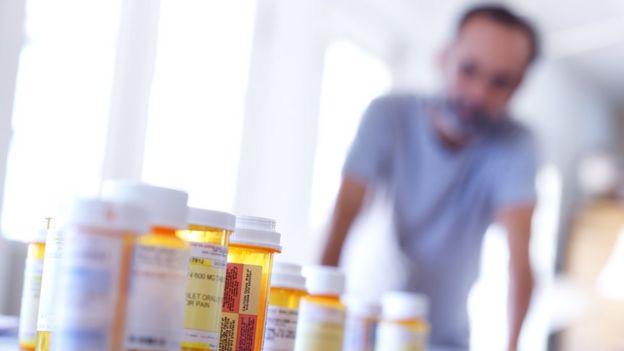 Un hombre mira a tubos con pastillas.