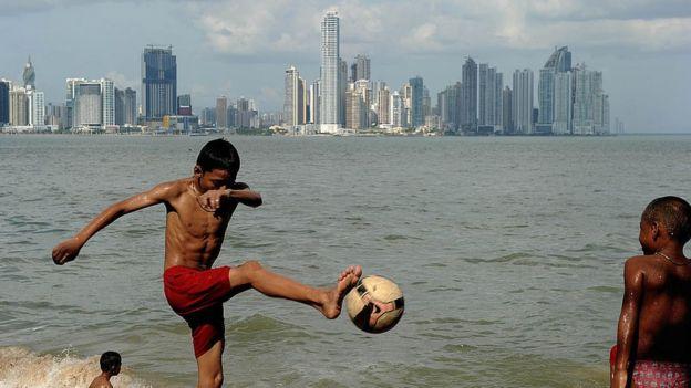 Niños panameños juegan fútbol frente a la bahía de Panamá