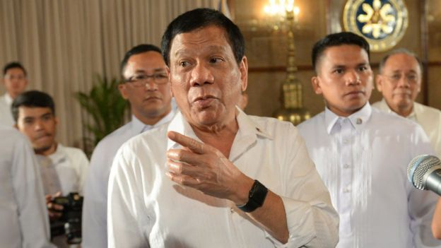 Philippine President Rodrigo Duterte (C) gestures as he talks to members of the media