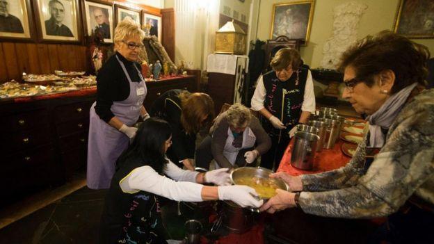 Mujeres preparan comida para los menos favorecidos en ocasión de Navidad.