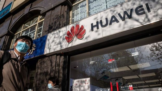 A man walks past a Huawei store