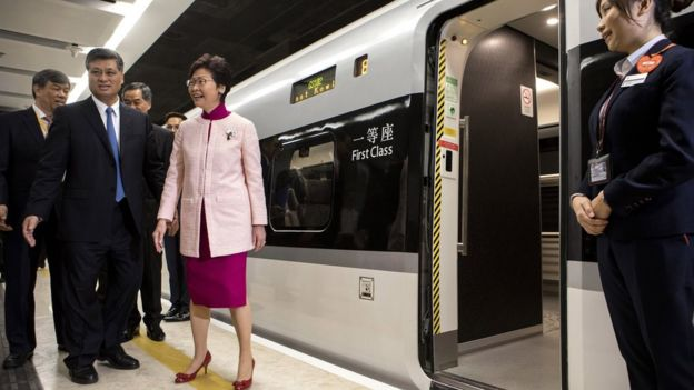 Ma Xingrui, governor of Guangdong Province, front row left, and Carrie Lam, Hong Kong's chief executive, centre, stand next to a Guangzhou-Shenzhen-Hong Kong Express Rail Link (XRL) train bound for Guangzhou Nan Station on a platform at West Kowloon Station in Hong Kong, China, 22 September 2018