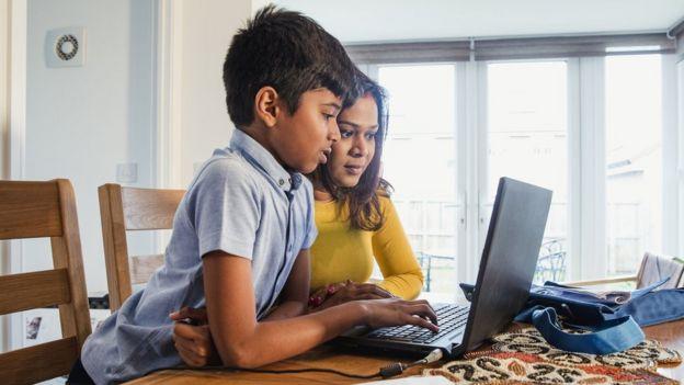un niño y una niña usando una computadora.