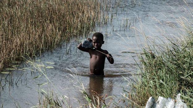 Niño cruzando un río.