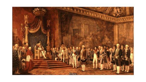 Esta pintura de Napoleão no Palácio de Versalhes, em 1809, mostra o imperador francês sentado enquanto todos ao lado permanecem em pé
