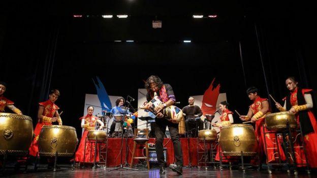 محسن شریفیان در حال نواختن نیانبان همراه گروه درام چین