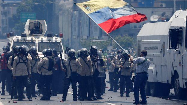 Un hombre ondea la bandera de Venezuela ante un grupo de guardias nacionales con equipos antimotines.