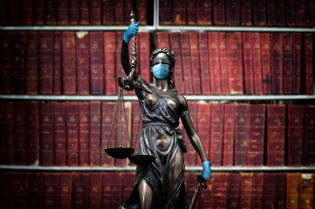 Escultura de la Justicia usando mascarilla