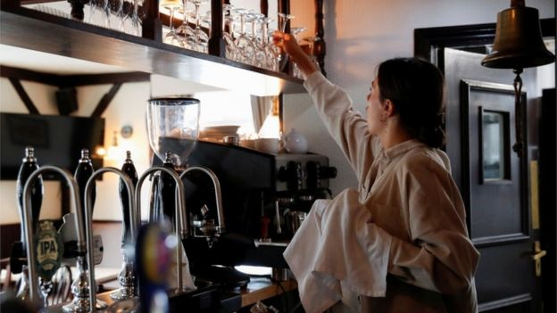A woman cleaning wine glasses behind a bar