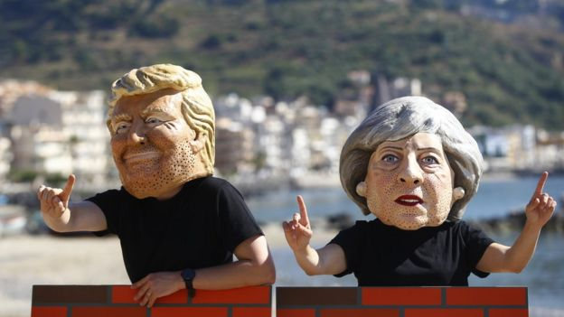 Manifestantes llevan máscaras de Theresa May y Donald Trump