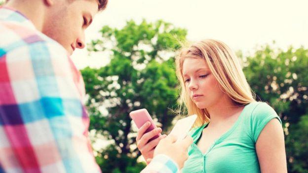 Genç kadın ve erkek telefonlarına bakıyor
