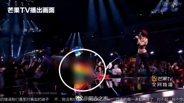 Screenshot of Switzerland's Eurovision performance with a rainbow flag in the audience blurred out and circled