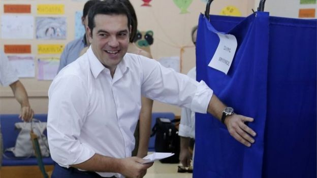 Leader of leftist Syriza party Alexis Tsipras holds his ballot as he enters the polling booth before voting for the general elections at a polling station in Athens, Greece, on 20 September 2015.