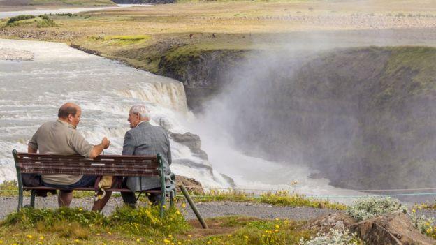 Dos hombres conversando en un banco de Islandia.