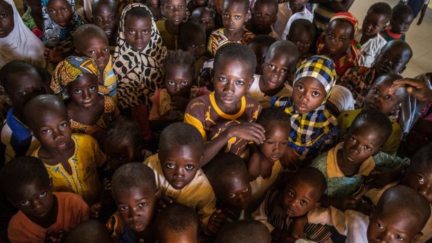 A group of children are seen posing in their classroom for a photo in the remote village of Kpalong