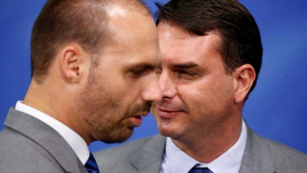 Eduardo Bolsonaro e Flavio Bolsonaro de perfil, engravatados, em evento