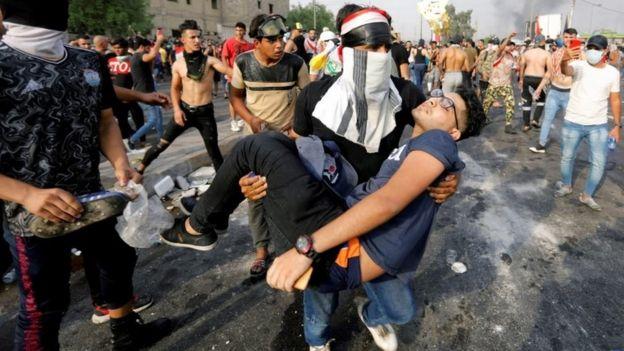 رجل يحمل متظاهرا مصابا